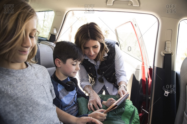 Mother assisting son in using digital tablet inside car while on road trip