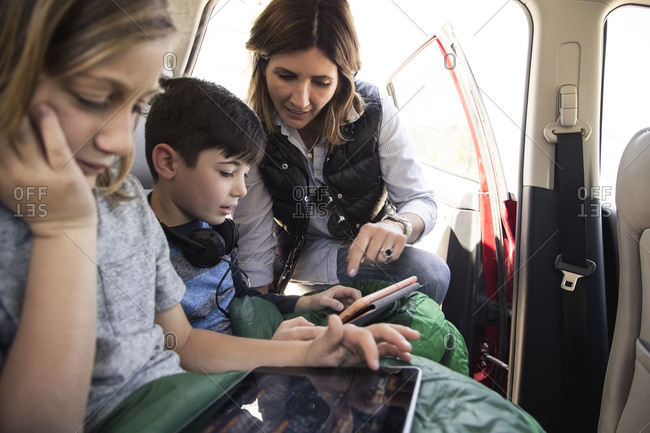 Woman assisting son in using digital tablet inside car while on road trip