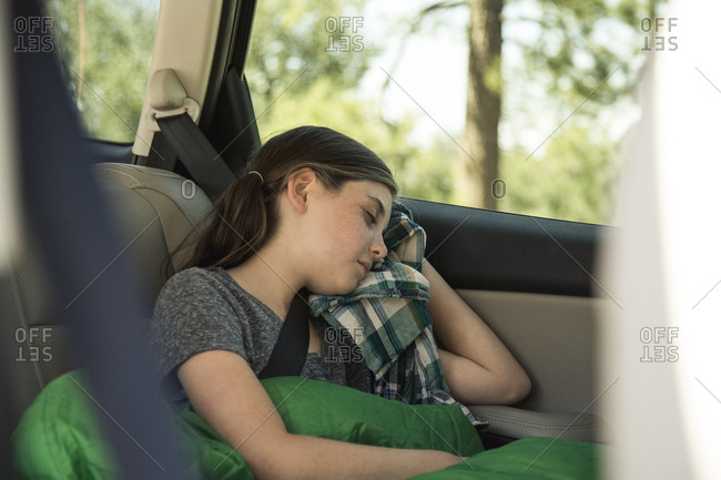 Relaxed girl sleeping in back seat of car while traveling