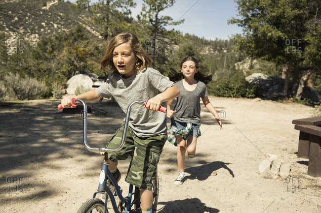 Girl running while brother riding bicycle at campground