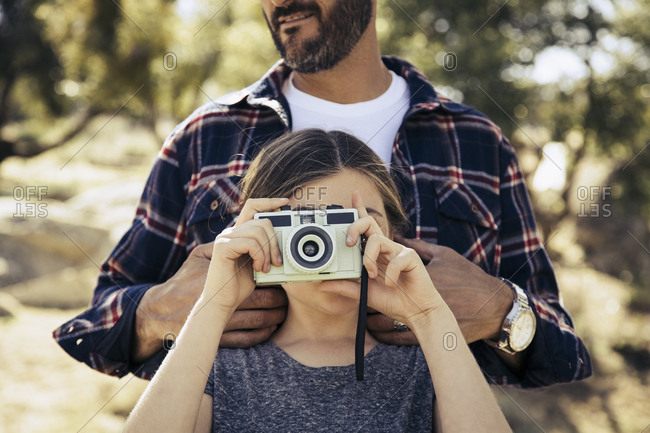 Girl photographing through vintage camera while standing with father in forest