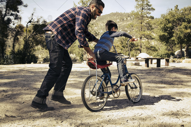 Happy father teaching son to ride bicycle on dirt path at campground