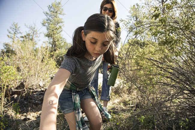 Girl hiking with mother in forest