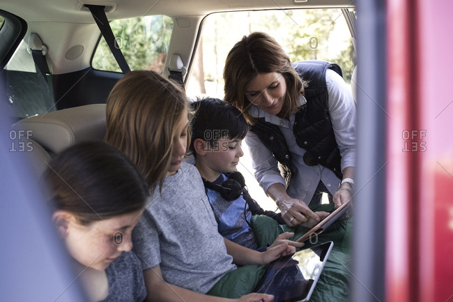 Mature woman assisting son in using digital tablet inside car while going on road trip