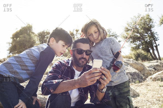 Father and sons looking at smartphone in forest