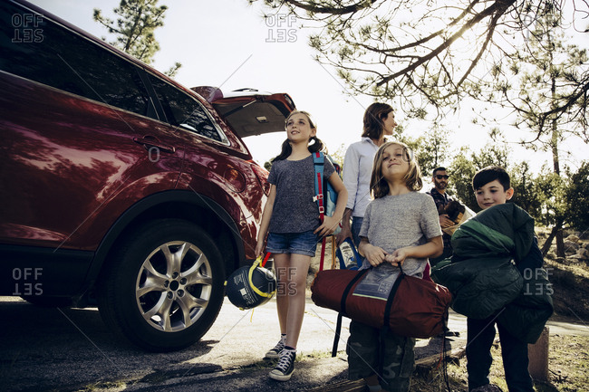 Family unloading camping gear from SUV in first