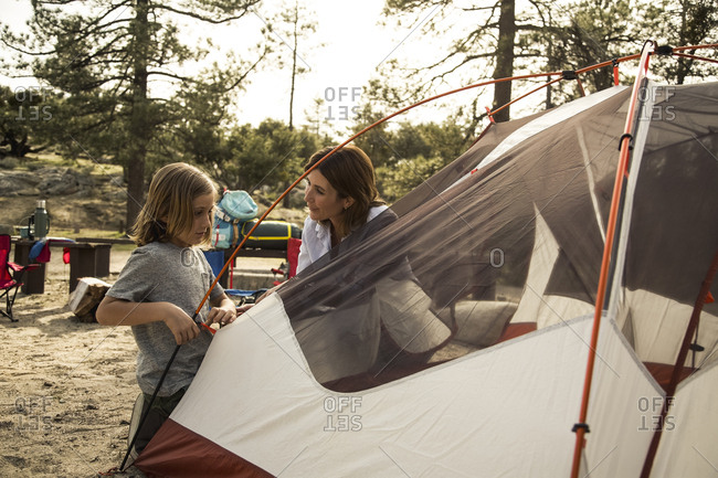 Mother and son setting up tent at campsite during summer vacation