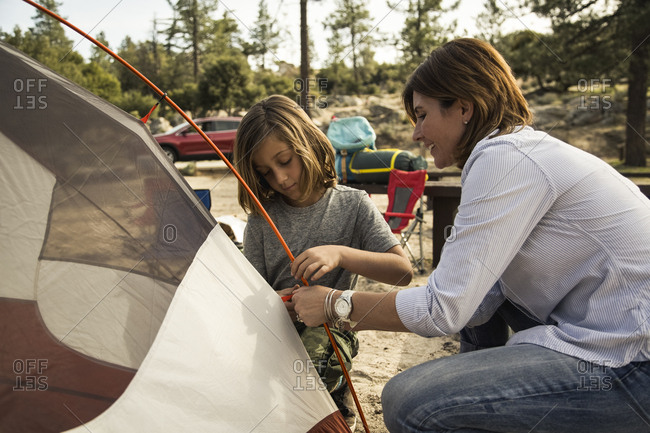 Mother and son preparing tent at campsite during summer vacation