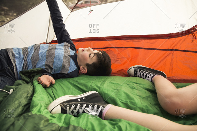 Boy lying with sister in tent while camping