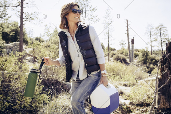Mature woman with cooler and water bottle walking in forest during camping