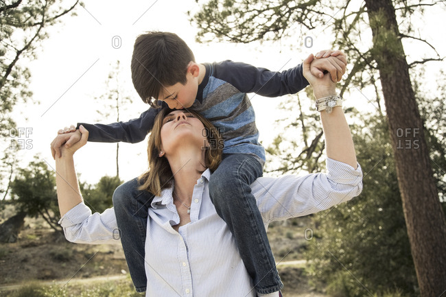 Boy kissing mother on forehead while sitting on shoulders in forest