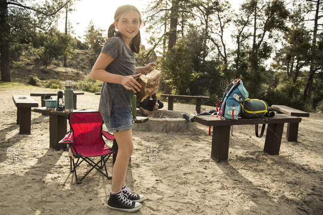 Full length portrait of girl holding firewood at campsite in forest