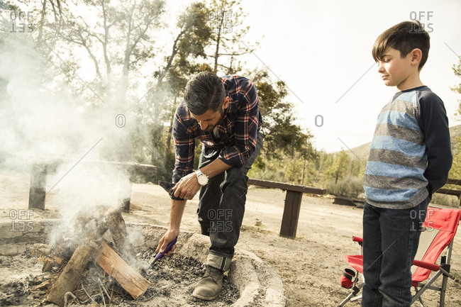 Boy watching father start campfire in forest