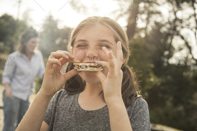Happy girl biting into a s'more at campground