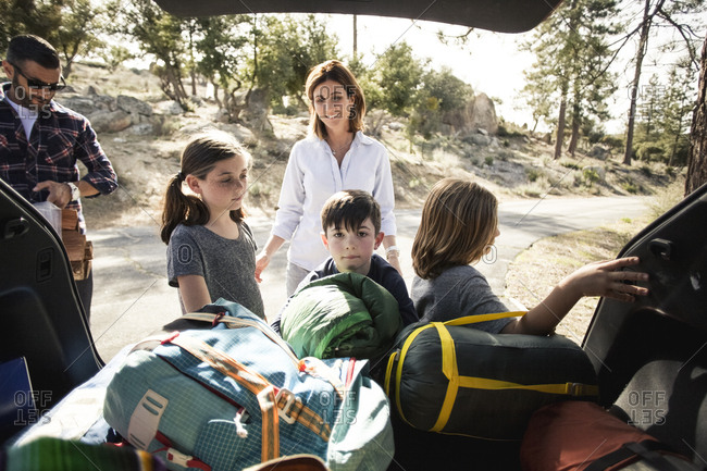 Parents and children standing by open car trunk loaded with camping gear