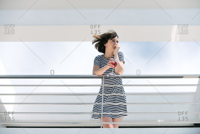 Women holding a glass of red wine looking out across a balcony