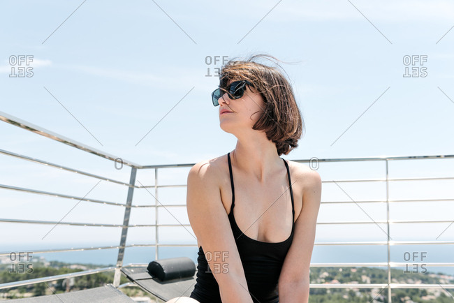 Young woman sitting outside in a black bathing suit and sunglasses