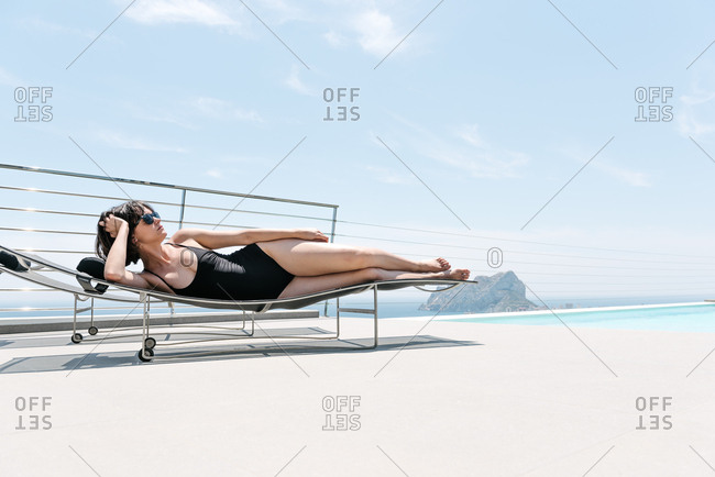 Young woman laying outside by a pool in a black bathing suit and sunglasses