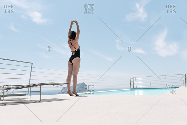 Young woman stretching by a swimming pool in a black bathing suit