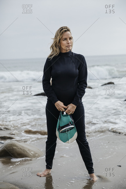 Full length of confident woman in wetsuit at the beach