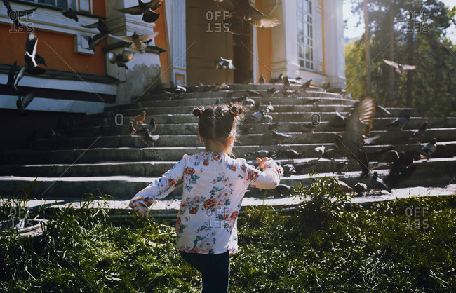 Girl running and pigeons flying at the old building