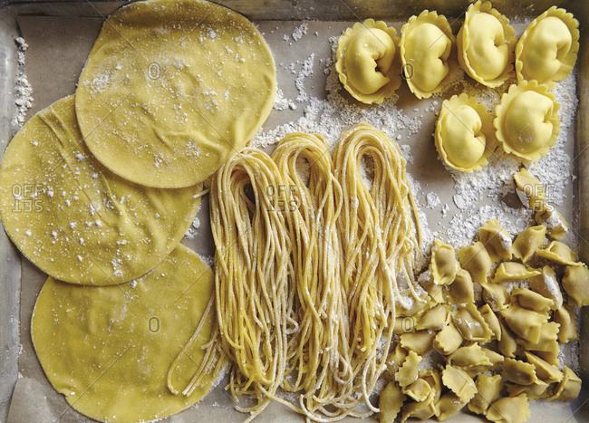 Variety of uncooked gluten free pasta on baking dish
