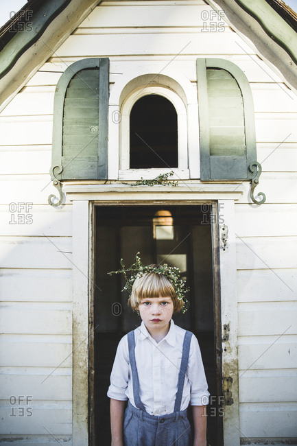 Boy standing in doorway of small house