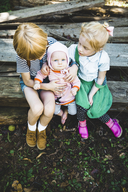 Three siblings sitting on wooden boards