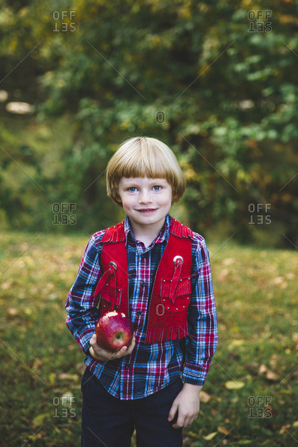 Happy boy eating an apple outdoors