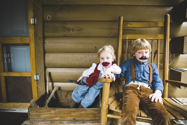 Kids dressed up with fake lips and mustache on porch of log cabin
