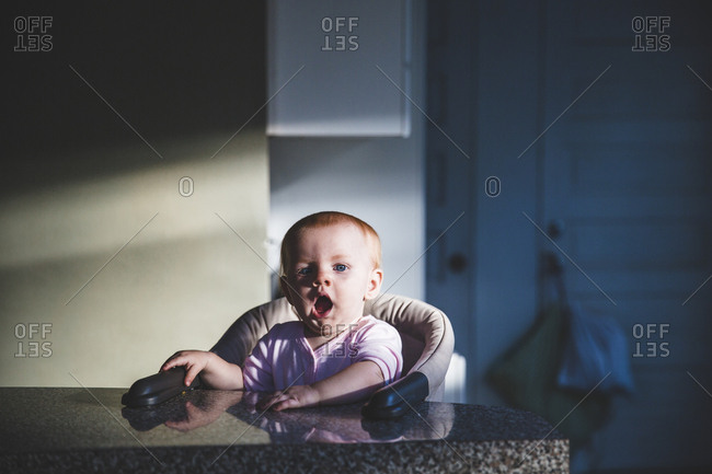 Baby sitting at booster seat on kitchen counter yawning