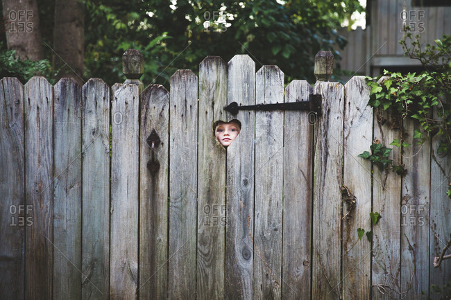 Boy looking through heart shaped hole in wooden fence