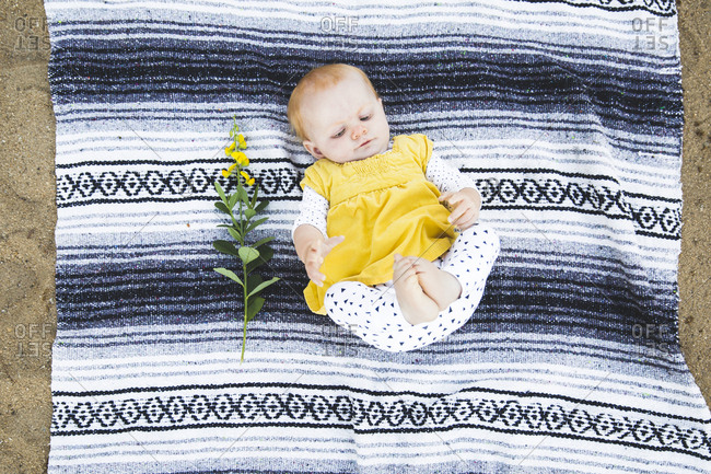 Baby lying on blanket beside yellow flowers