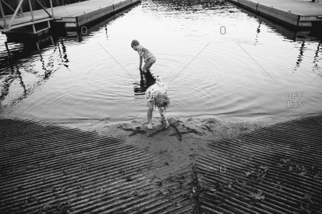 Two kids playing on beach with boat docks in black and white