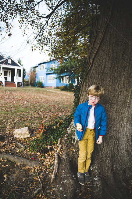 Boy standing by tree eating an apple
