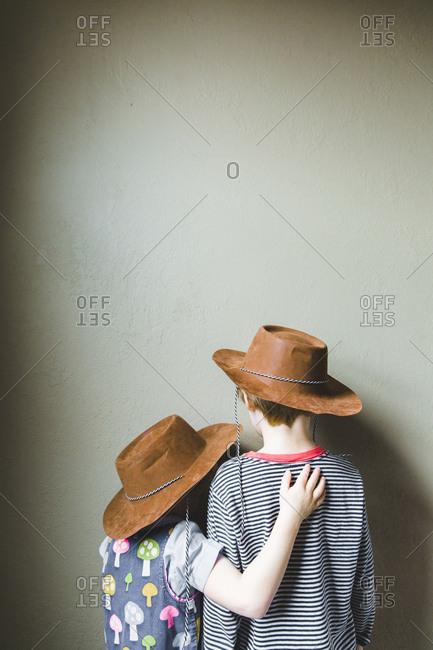 Rear view of two kids wearing cowboy hats