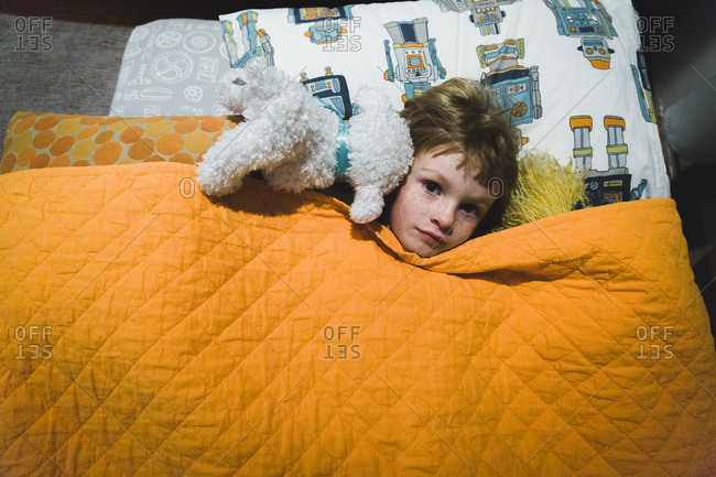 Boy in bed with orange blanket