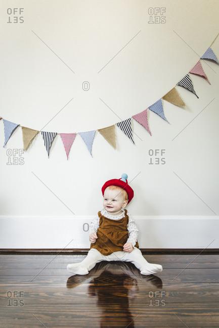 Baby sitting on floor under birthday banner