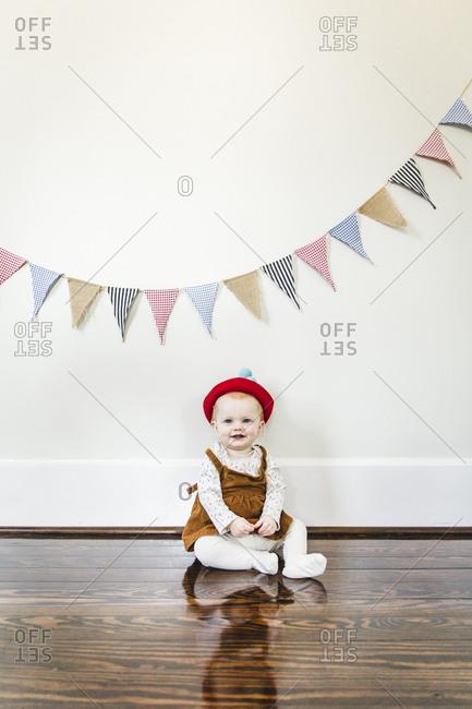 Baby sitting under birthday banner
