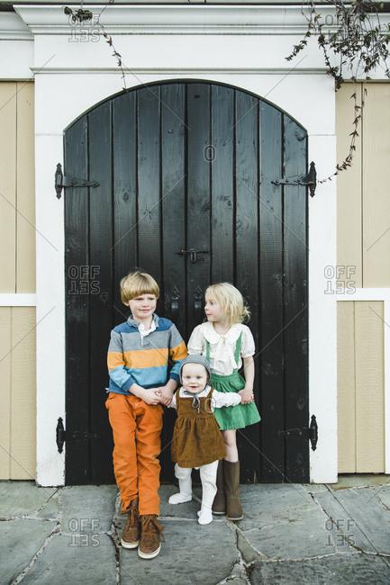 Two kids standing in front of black wooden door