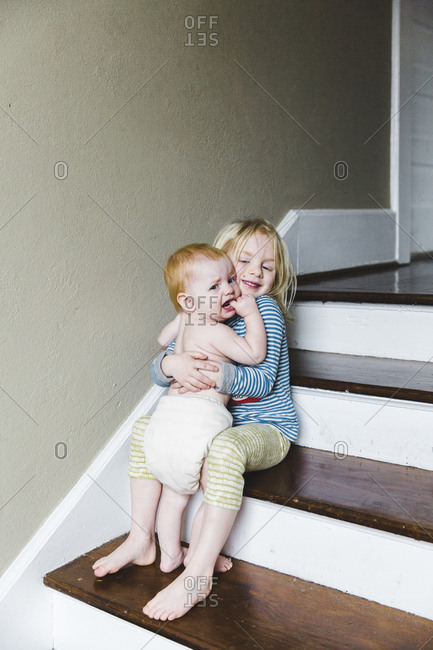Girl sitting on steps hugging baby sister