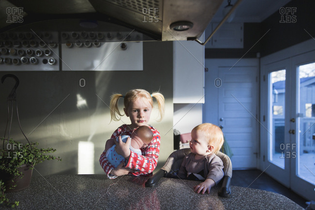 Girl sitting by baby sister holding baby doll