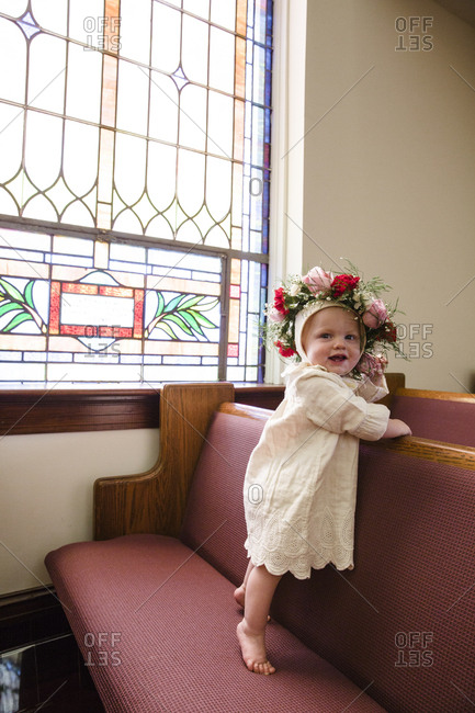 Happy baby standing on church pew wearing flower crown