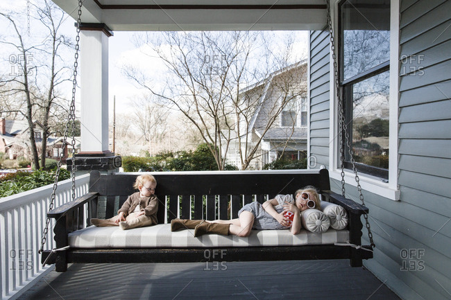 Two little girls on front porch swing