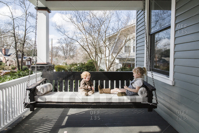 Two little girls sitting on front porch swing