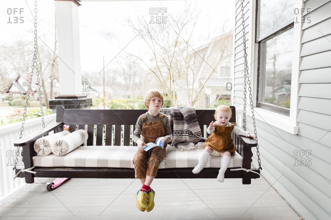 Two little kids sitting on front porch swing