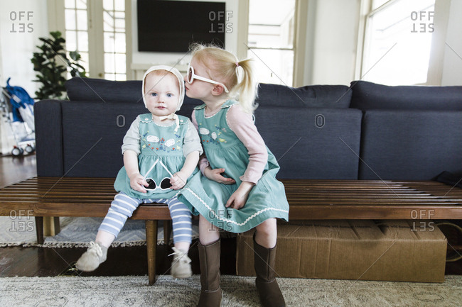 Girl kissing baby sister while wearing matching dresses
