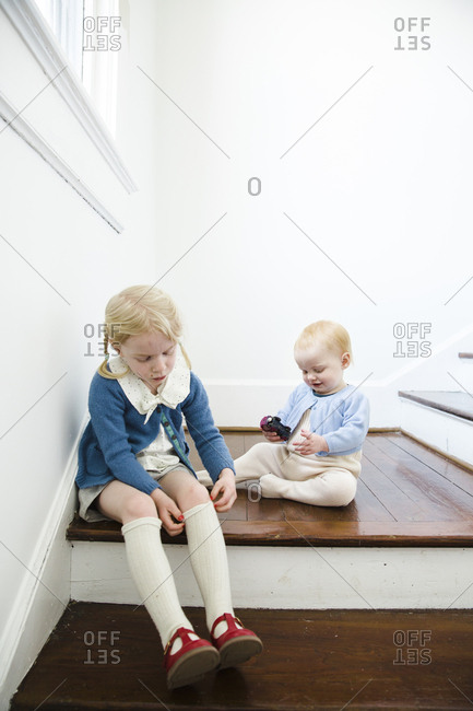 Girl putting stockings on while sitting on steps with baby sister
