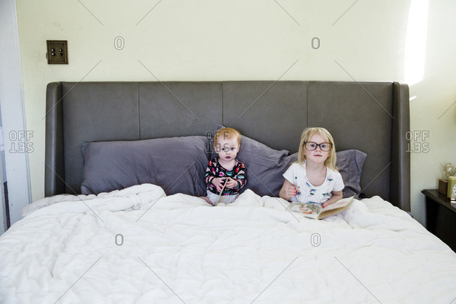 Young sisters sitting together in bed reading books