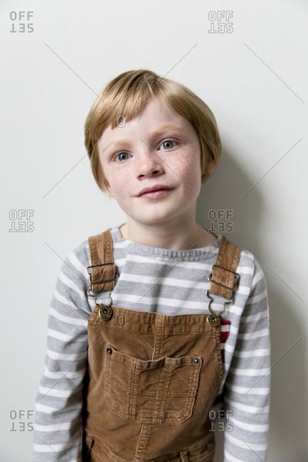Portrait of little boy wearing brown overalls